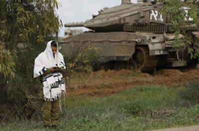 An Israeli soldier wearing a prayer shawl prays near a tank as troops take position on the Israeli-Gaza Strip border on December 30, 2008.